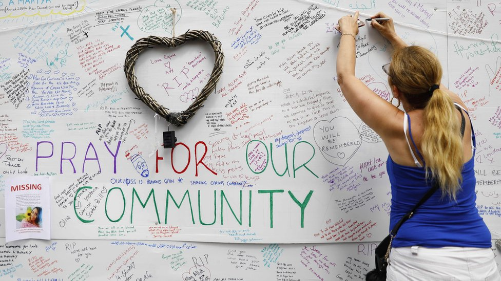 A woman writes on a message wall near to the Grenfell Tower block