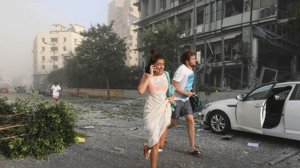 Dos personas huyen de la zona tras la explosión en el puerto de Beirut.