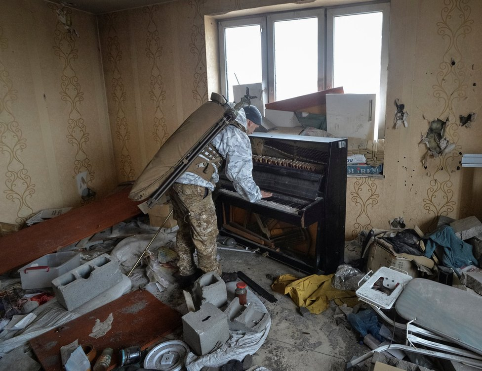 A soldier plays a piano in a damaged house