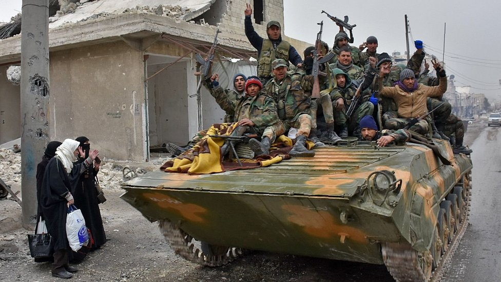 Syrian government forces ride through the Masaken Hanano district of Aleppo, on an armoured personnel carrier (30 November 2016)