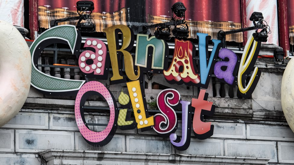 A brightly-coloured sign declaring the existence of Carnaval Aalst hangs upon a stone wall amid spotlights