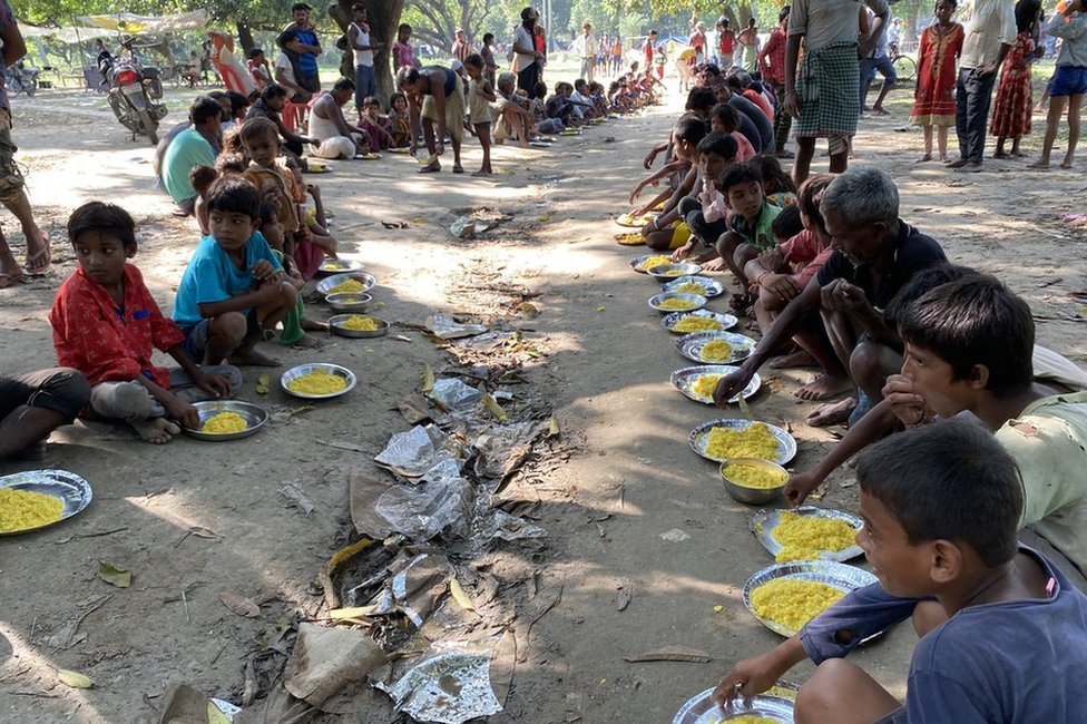 Children at the relief camp sit in the mud to eat their meals
