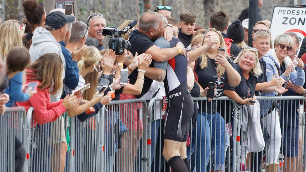 Gareth Thomas is embraced by his husband Stephen at the Ironman triathlon in Tenby, Pembrokeshire