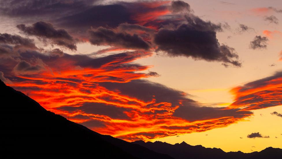 Nubes de rojo y naranja intenso, sobre unas montañas oscuras
