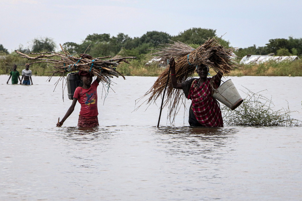 South Sudanese women walk in a flooded area that has been isolated for about a month and a half due to the heavy rain in Pibor Town