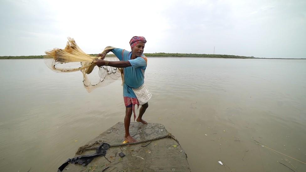 Pescador lanzando redes en el mar den Sundarbans