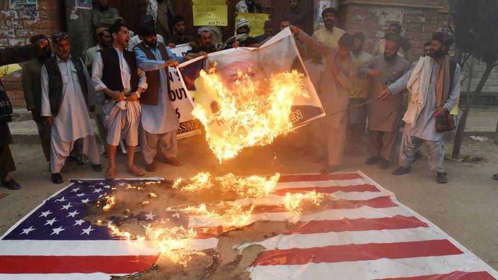 Pakistaníes protestan quemando la foto de Donald Trump y la bandera de EE.UU. por un bombardeo estadounidense en la ciudad afgana de Quetta.