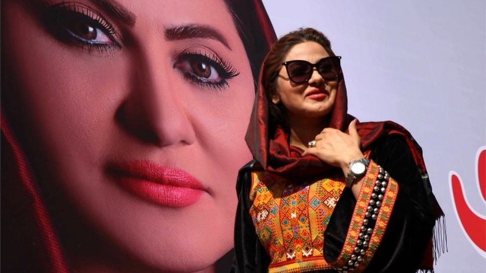 Seemi Barakzai, a candidate for the Afghan elections next to a poster of herself in the western city of Herat.