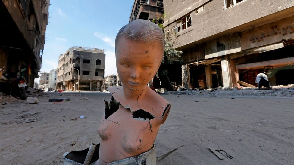A mannequin stands near destroyed buildings in the Yarmuk Palestinian refugee camp in the Syrian capital Damascus as the regime began to clean the wreckage from the camp on October 09, 2018.