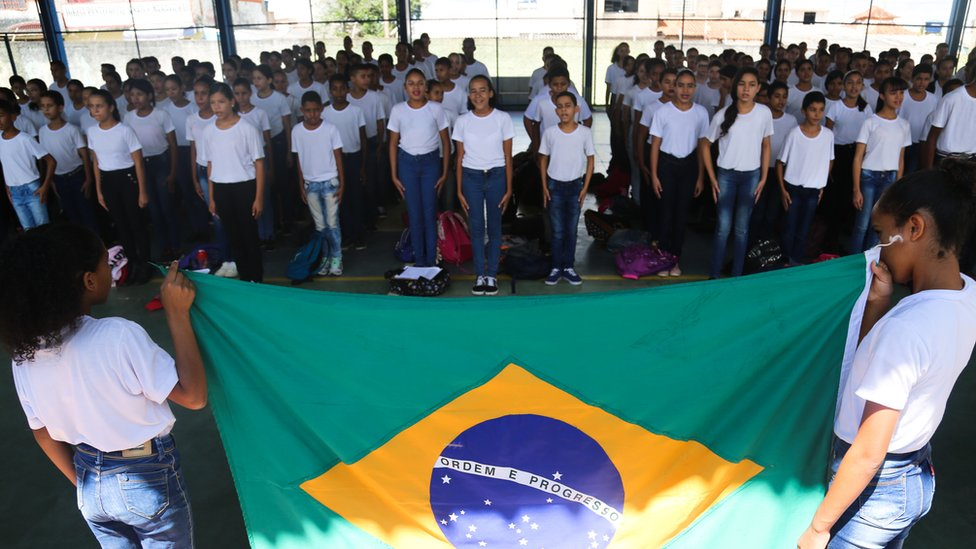 Brazilian students sing the national anthem