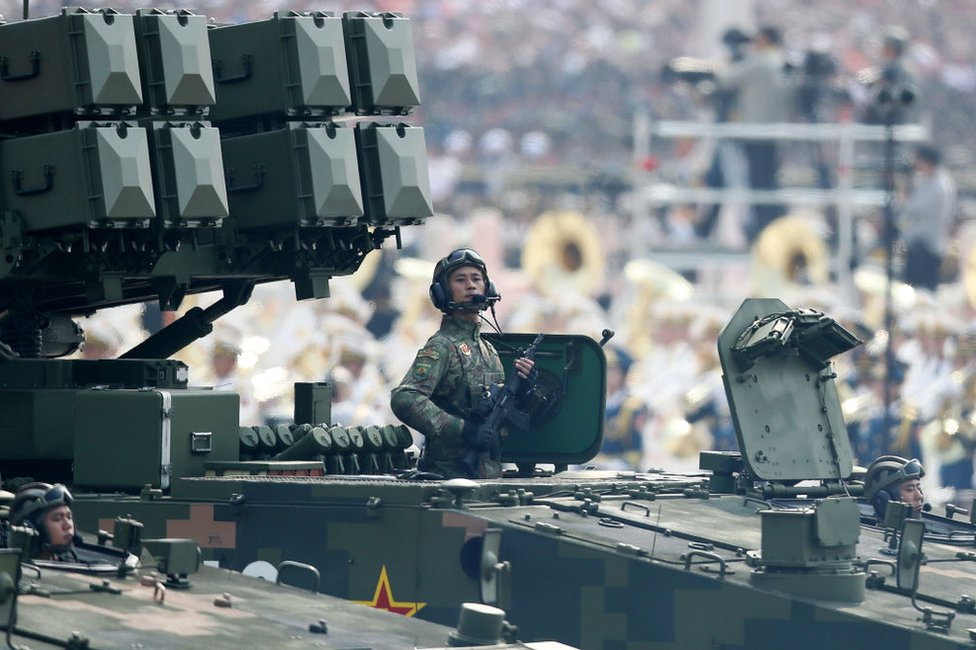 A soldier of the People's Liberation Army stands to attention on a tank during a parade to celebrate the 70th anniversary of the founding of the People's Republic of China in 1949, at Tiananmen Square in Beijing on 1 October 2019.