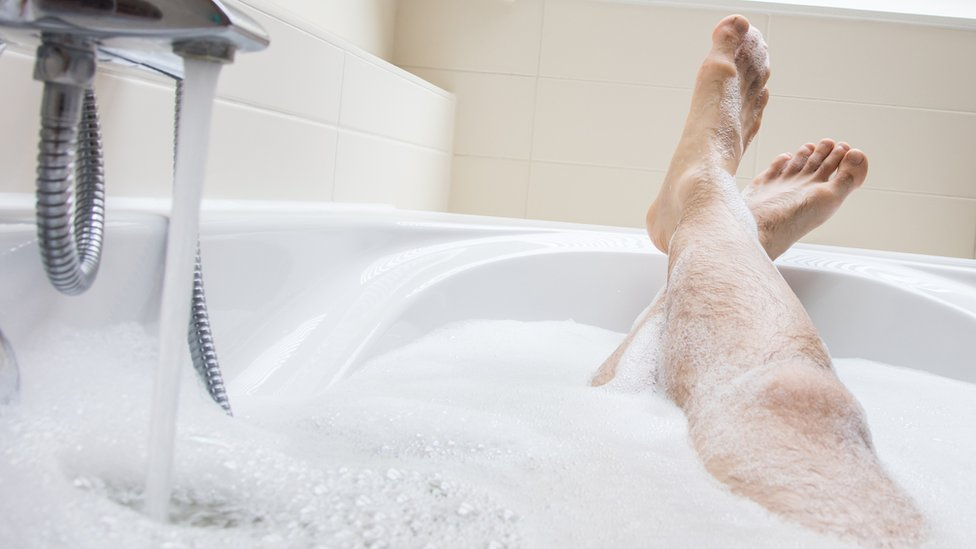 أقدام رجل في حوض استحمام