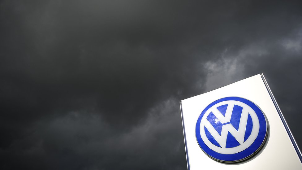 Volkswagen sign with storm clouds behind