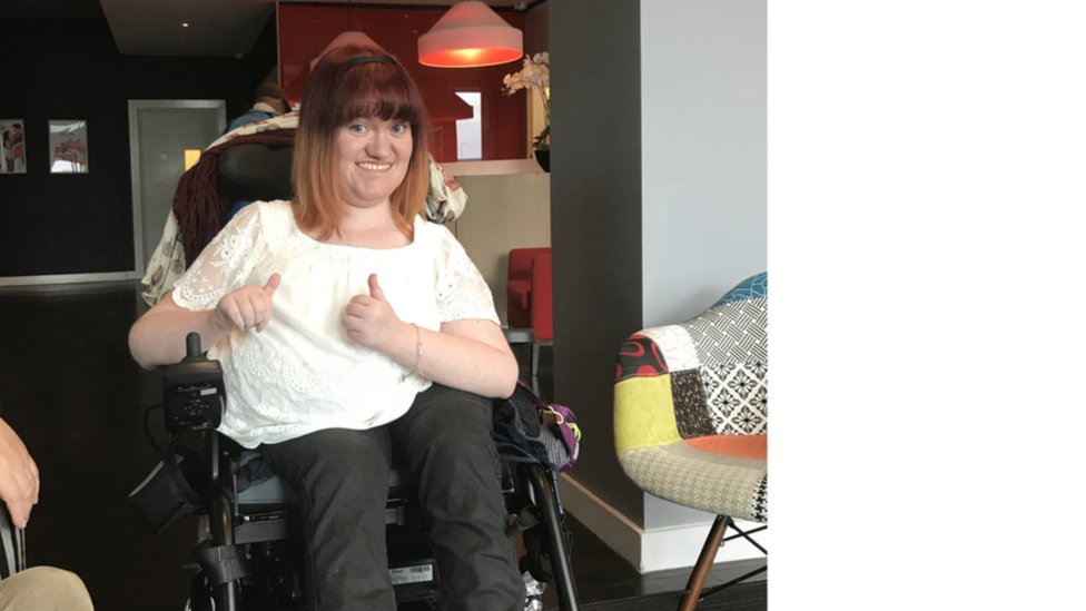 Michaela sitting in her wheelchair giving two thumbs up
