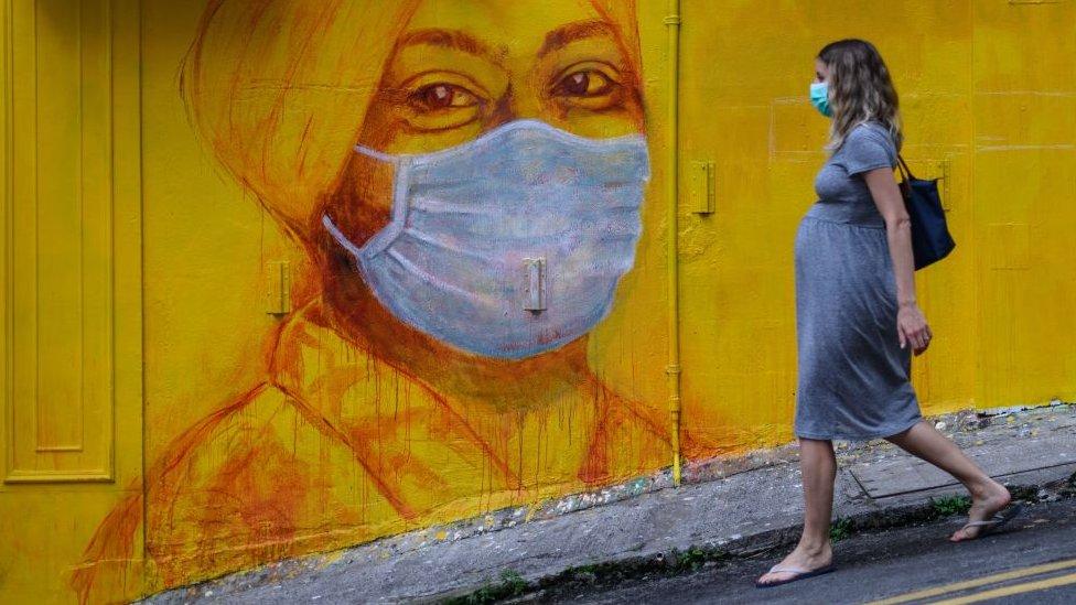 香港街頭戴口罩的路人與壁畫相呼應