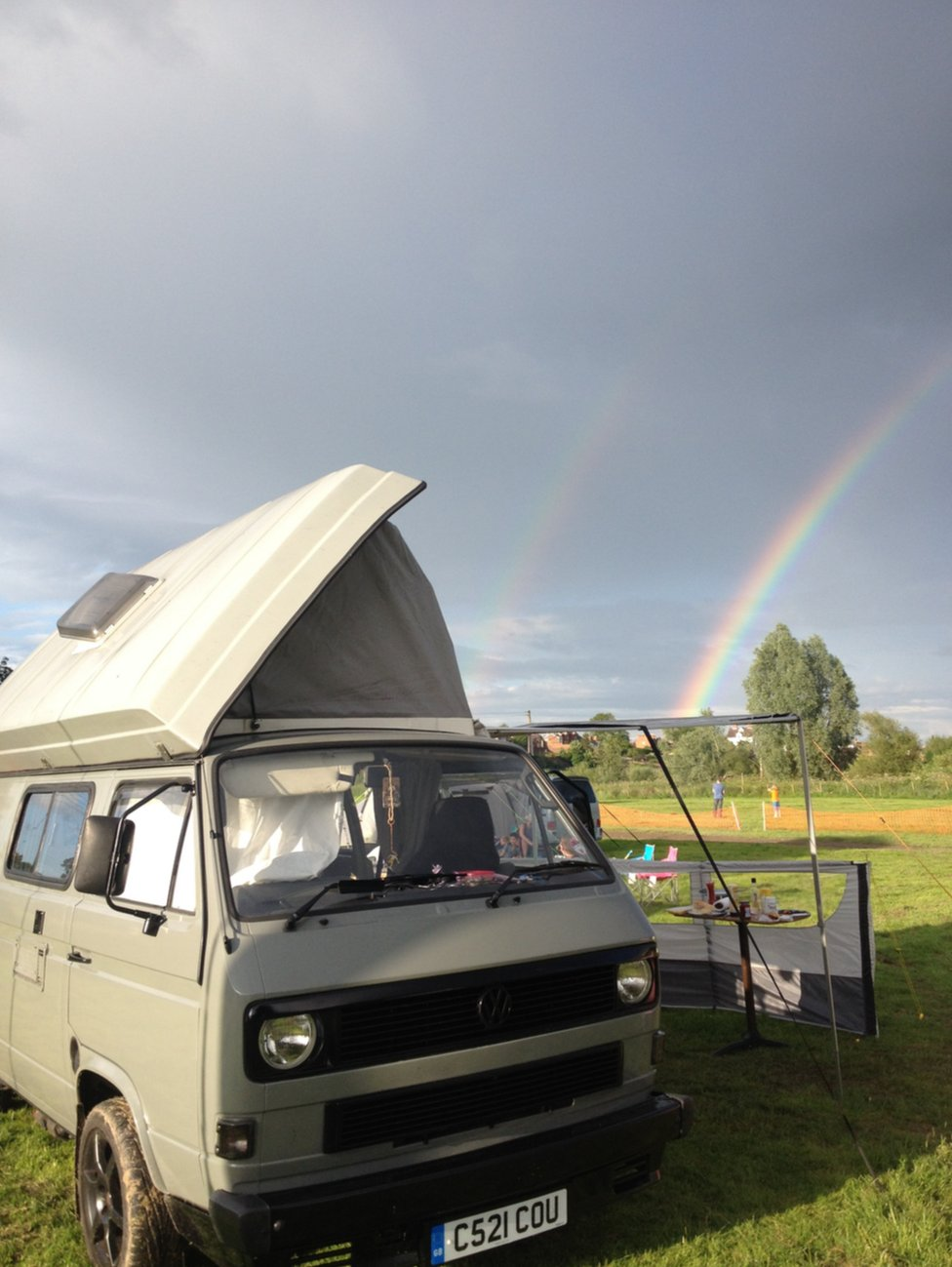 A campervan is parked up on a field with a double rainbow in the distance