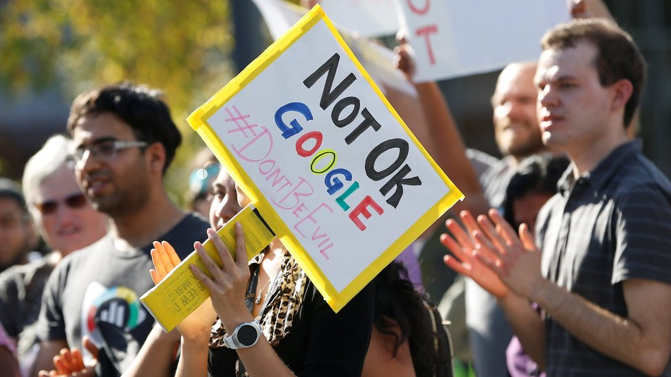 """A Google employee (centre) holds a sign that reads """"Not OK Google"""" during a walkout in Mountain View, California"""