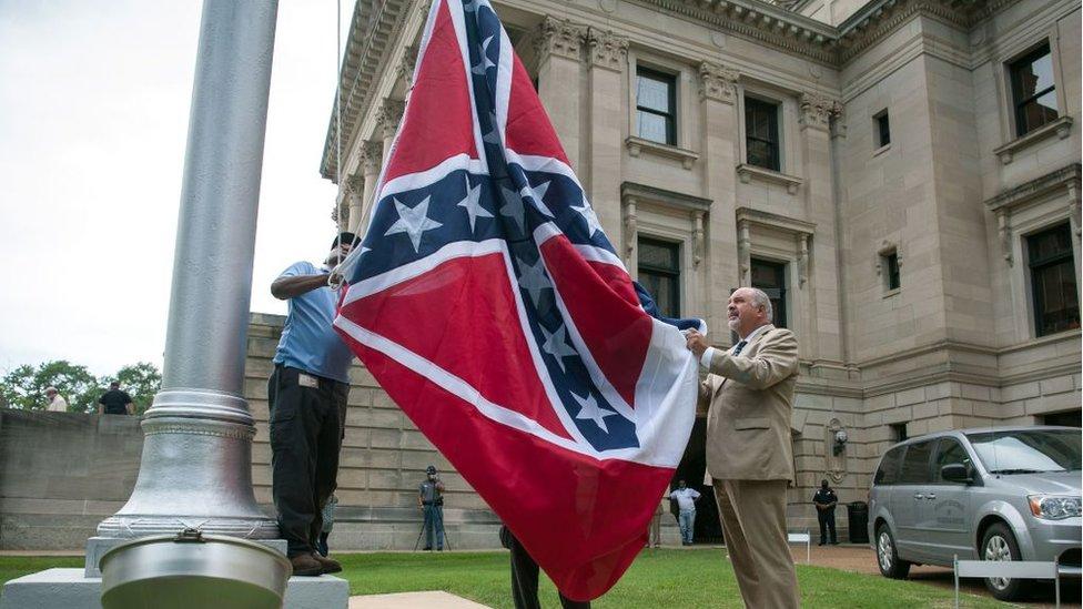 Autoridades estatales bajan del asta la bandera confederada de Mississippi.