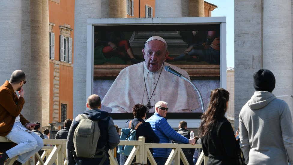 {eople watch a screen live-broadcasting Pope Francis's Sunday Angelus prayer in St. Peter' s Square at the Vatican