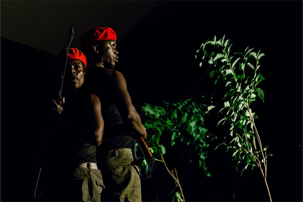 """Actors play two red berret soldiers with assault rifles searching for innocent civilians who have deserted their homes hiding in the thick bush on June 2, 2018, in Harare, as they take part in a scene from a play """"1983 the Dark Years"""", which portrays the life of a young girl affected by the Gukurahundi events in the 1980s when human rights atrocities were perpetrated by the Zimbabwe National Army deployed to put down a dissident military group in the Matebeleland region of the country."""