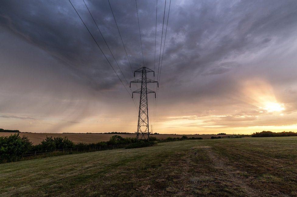 Dark clouds over a pylon in a field