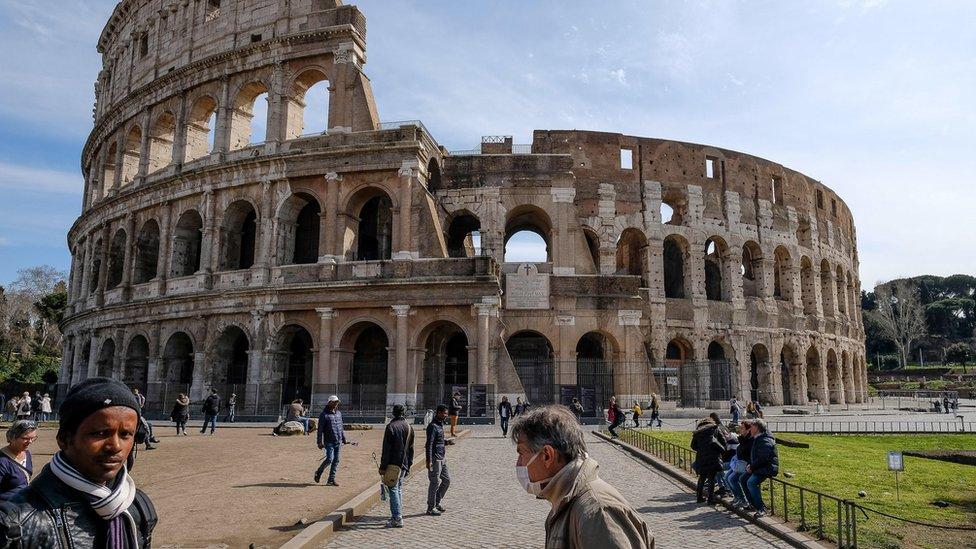 A tourist wears a face mask in front of the Colosseum in Rome, Italy