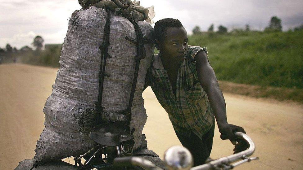 Joven con bolsa de carbón en bicicleta.