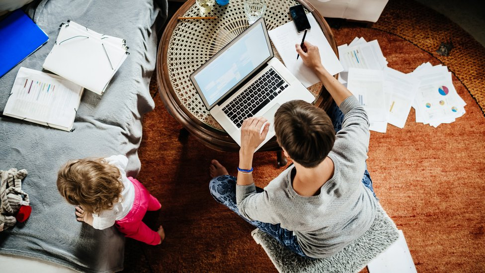 Hombre trabajando desde casa con su hija al lado