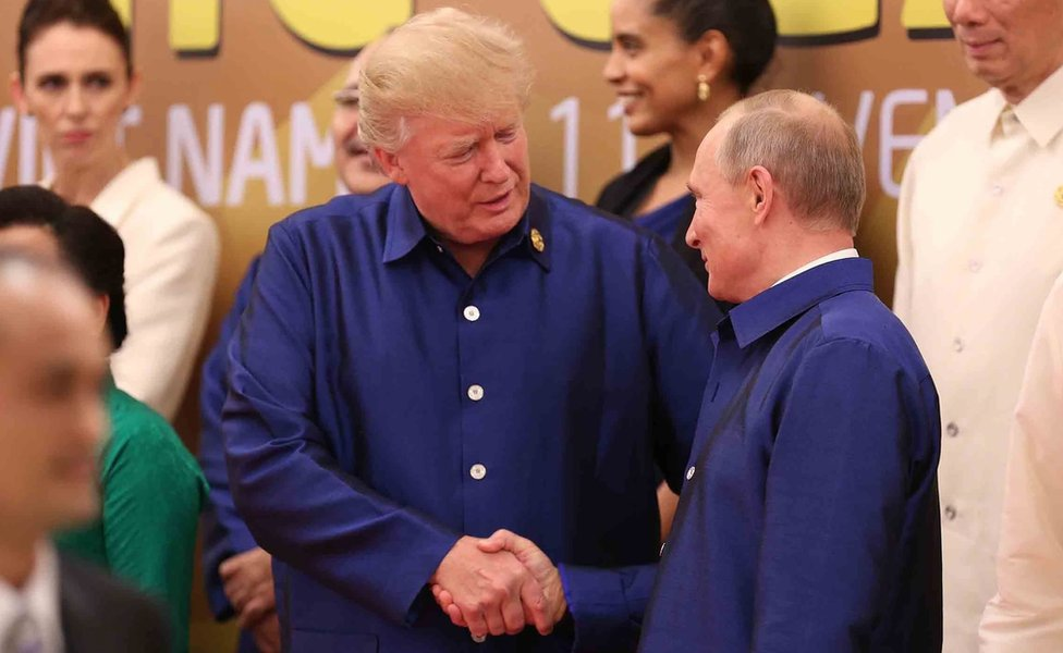 US President Donald Trump (L) shakes hands with Russia