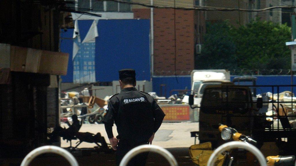 Policajac ispred pijace u Vuhanu