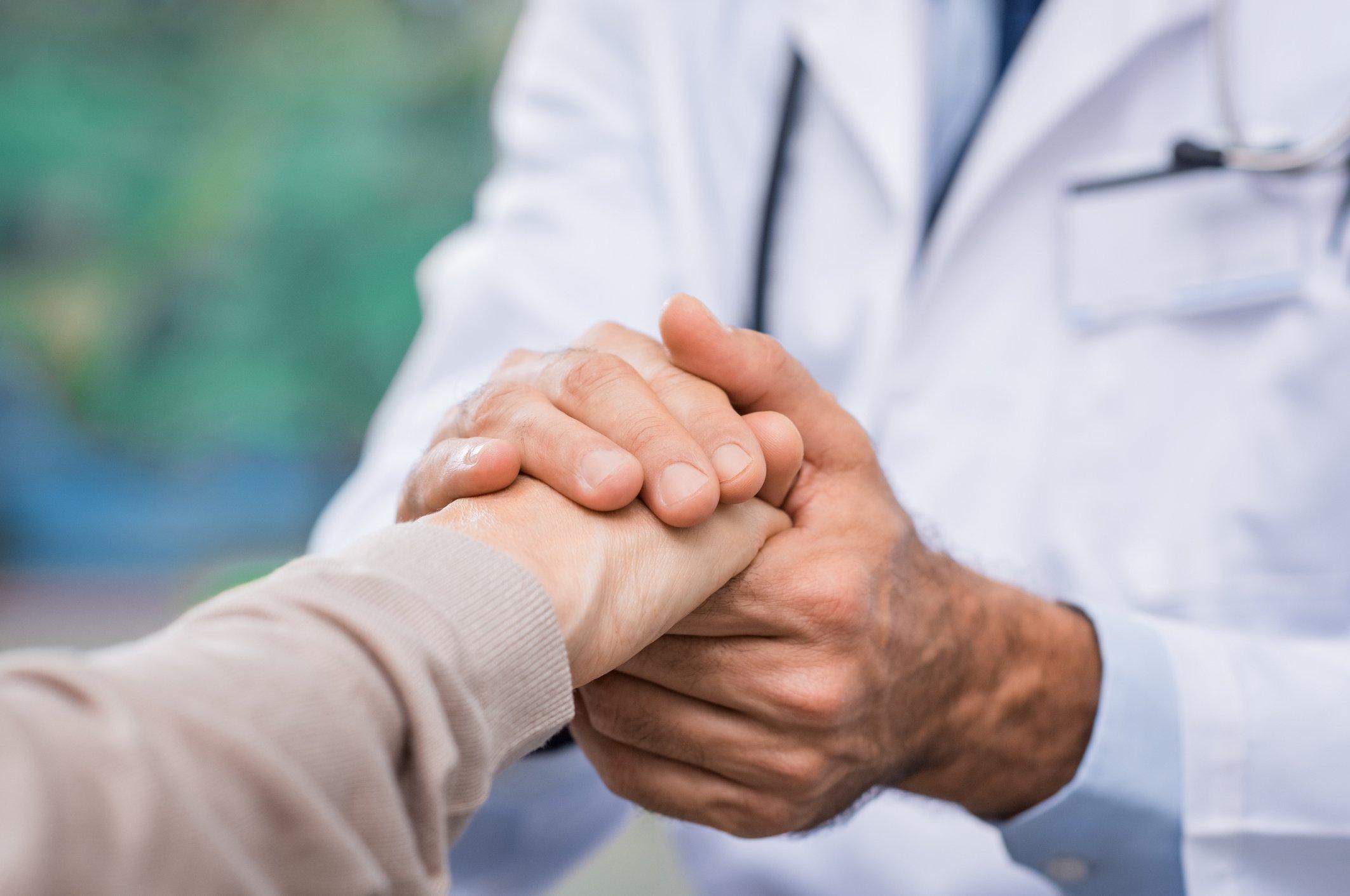 Un médico tomando la mano de una persona