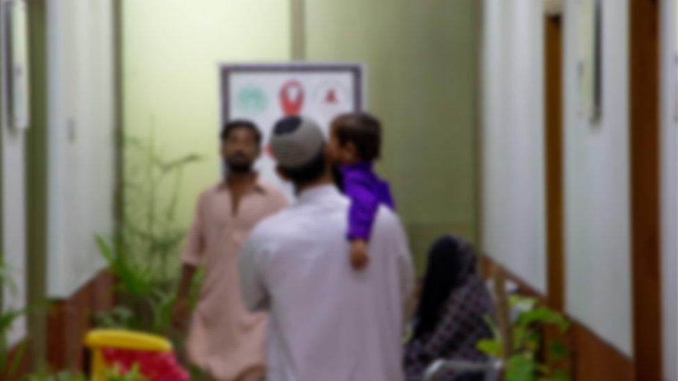 Un hombre con un niño en una clínica de Pakistán.