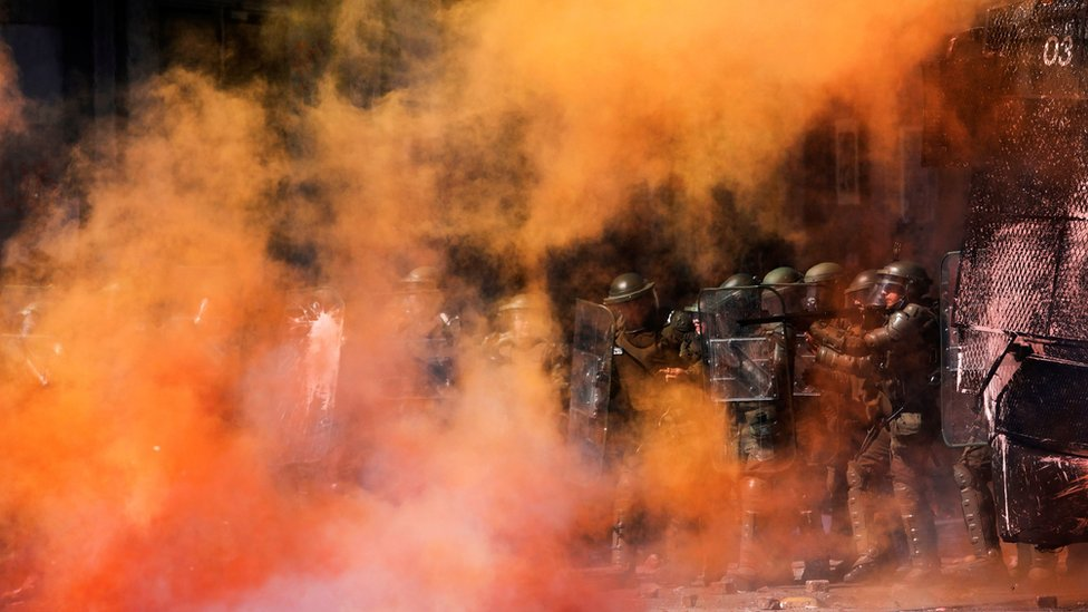 Riot police stand amid tear gas and smoke from a burning barricade during a protest against Chile's government in Concepcion on 12 November, 2019