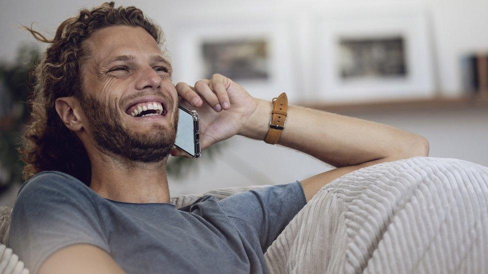 رجل يضحك أثناء التحدث على الهاتف في هذه الصورة المخزنة