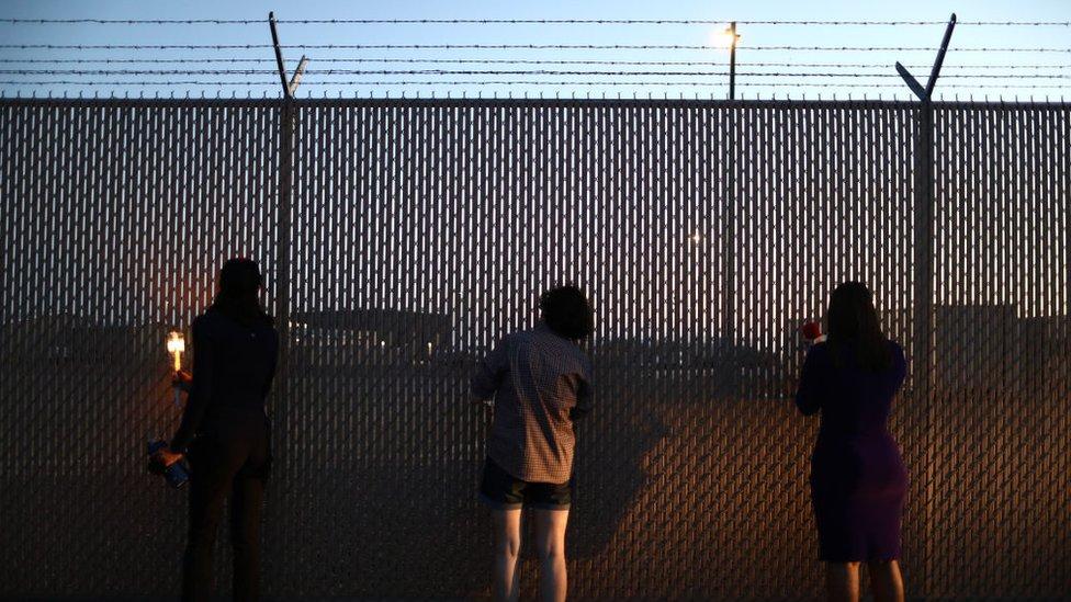 Ljudi gledaju kroz ogradu koja obezbeđuje stanicu granične policije u Klintonu, Teksasu