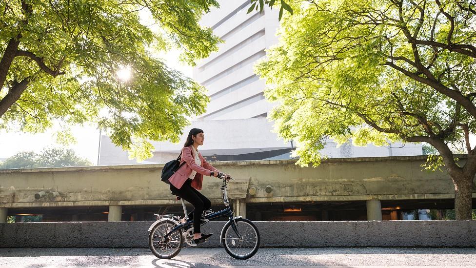 Mujer en bicicleta en una ciudad con árboles