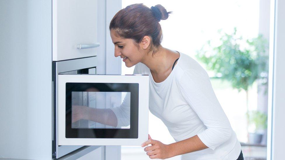 Mujer cocinando al microondas