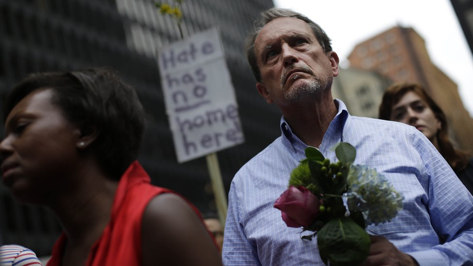 """a man holding flowers in front of a sign that reads """"Hate has no home here"""""""