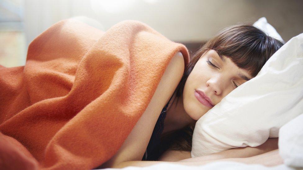 Mujer durmiendo sobre almohada y cubierta con un manto naranja