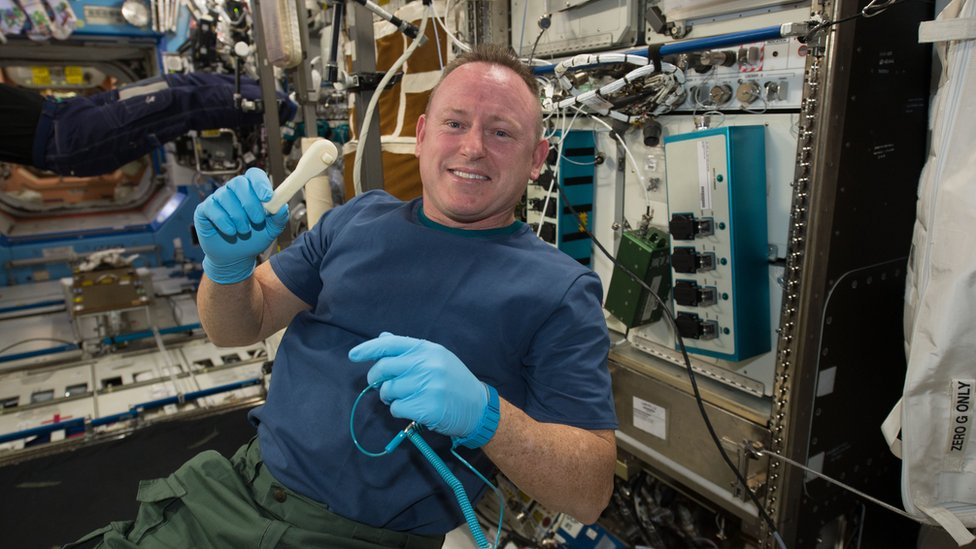 Astronaut Barry Wilmore shows off a ratchet wrench made with a 3D printer on the ISS