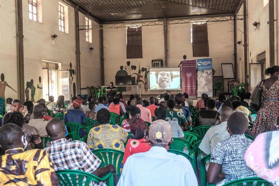 People watch the verdict in Gulu.