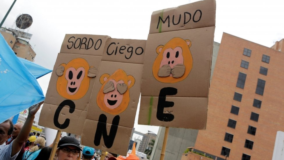 "Opposition supporters hold placards during a rally to demand a referendum to remove President Nicolas Maduro in Caracas, Venezuela, May 14, 2016. The placards (L-R) read ""Deaf"", ""Blind"" and ""Dumb"". ""CNE"" on the placards refers to the National Electoral Council. REUTERS"