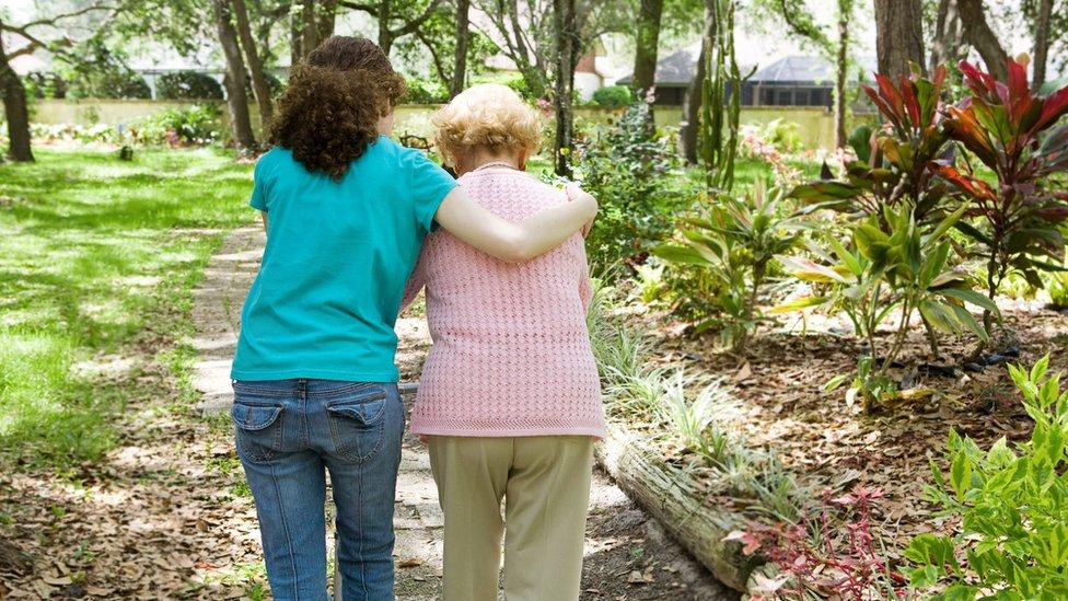Mulher ampara idosa durante caminhada