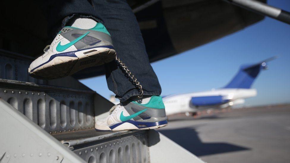 Una persona deportada de Estados Unidos y con unas esposas alrededor de los pies aborda un avión de regreso a su país de origen.