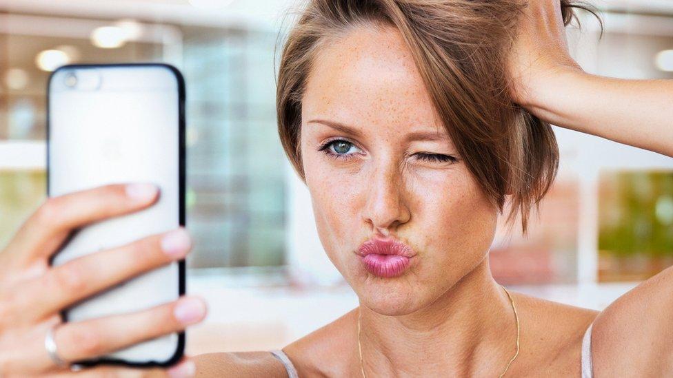 Una chica tomándose un selfie con el celular