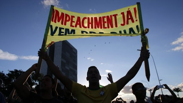 """An anti-government protestor holds a sign that reads in Portuguese """"Impeachment now!"""