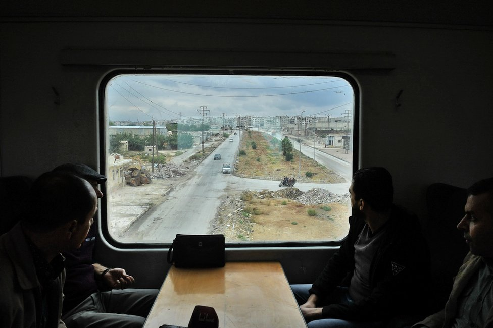 Passengers look out of a train window on to a damaged Aleppo skyline