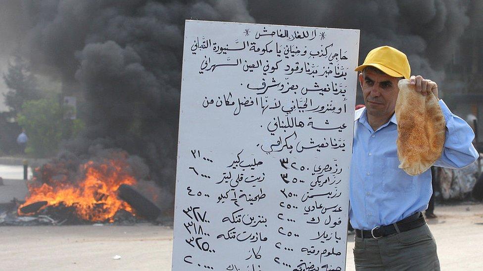 Un hombre sostiene un pan y un cartel durante protestas por los precios de los alimentos en Líbano, 7 mayo de 2008