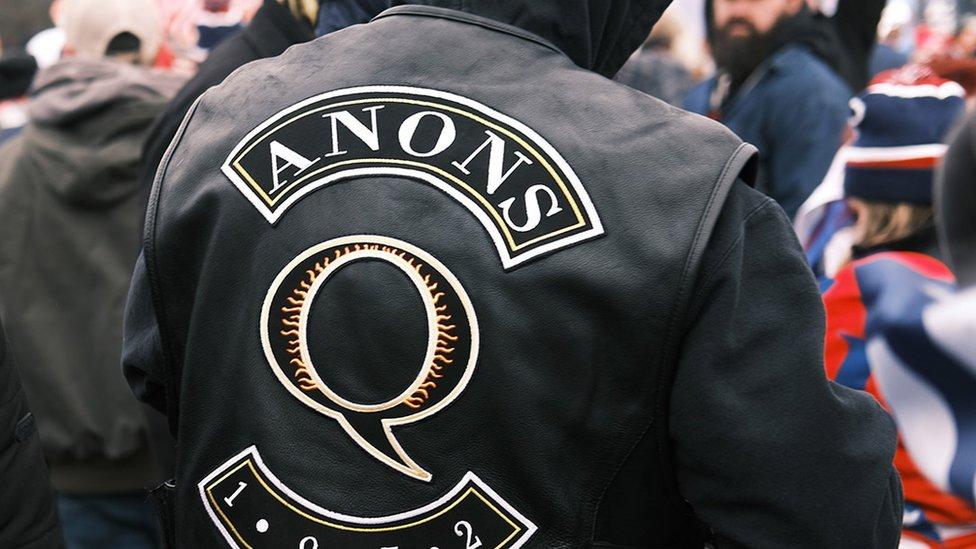 Persona fotografiada desde atrás con chaqueta QAnon