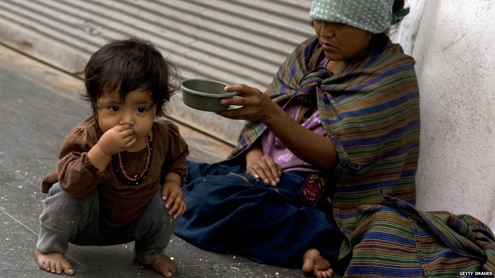 Small child with an adult who is begging on the street